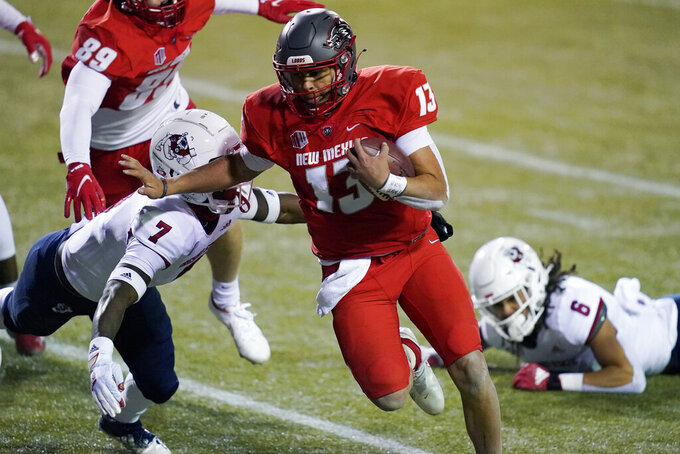 New Mexico quarterback Isaiah Chavez (13) runs by Fresno State defensive back Reggie Strong (7) for a touchdown during the first half of an NCAA college football game Saturday, Dec. 12, 2020, in Las Vegas. (AP Photo/John Locher)
