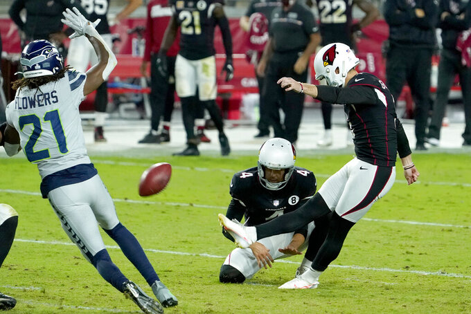 Arizona Cardinals kicker Zane Gonzalez kicks the game winning field goal as punter Andy Lee (4) holds during the second half of an NFL football game against the Seattle Seahawks, Sunday, Oct. 25, 2020, in Glendale, Ariz. The Cardinals won 37-34 in overtime. (AP Photo/Rick Scuteri)