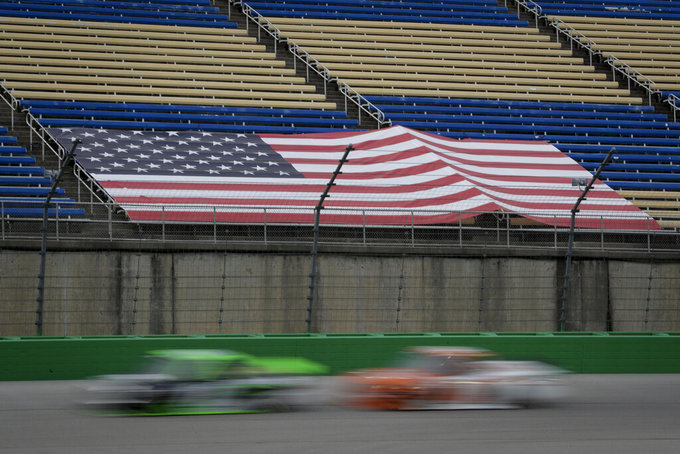 Drivers run past an empty grandstand during a NASCAR Truck Series race Saturday, July 11, 2020, in Sparta, Ky. (AP Photo/Mark Humphrey)